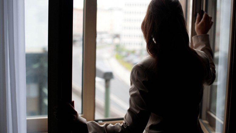 Business woman is looking out of the window in her hotel room.