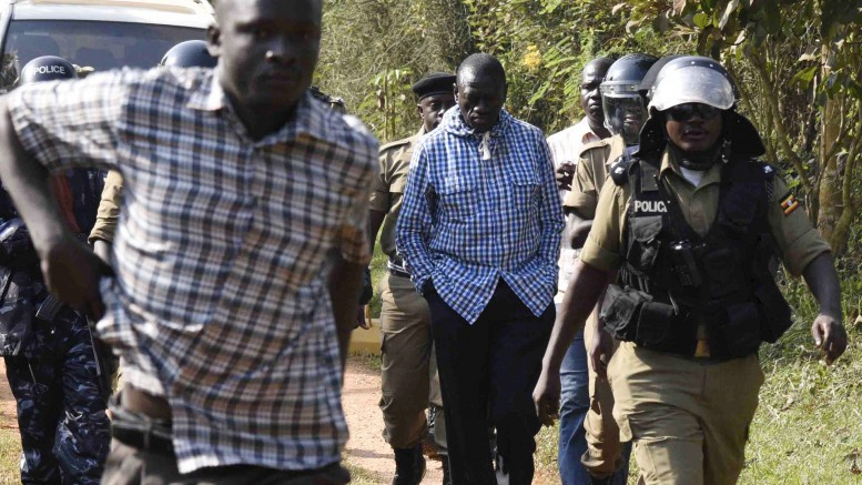 Opposition leader Kizza Besigye is escorted by Ugandan policemen to a police vehicle outside his house at the outskirts of Kampala