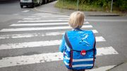 A girl is waiting at a zebra crossing on her way to school.