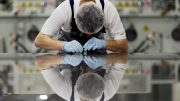 A worker of Signet Solar checks a photovoltaic module in a plant in Mochau near Dresden