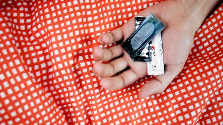 Hand with condoms in bed