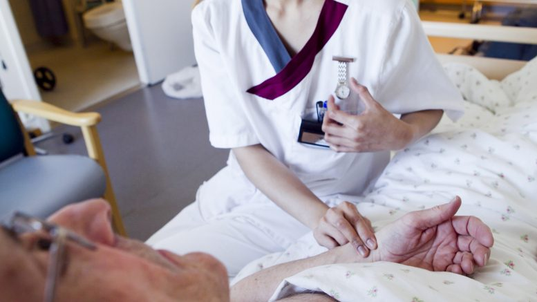 Health worker takes the pulse of male patient