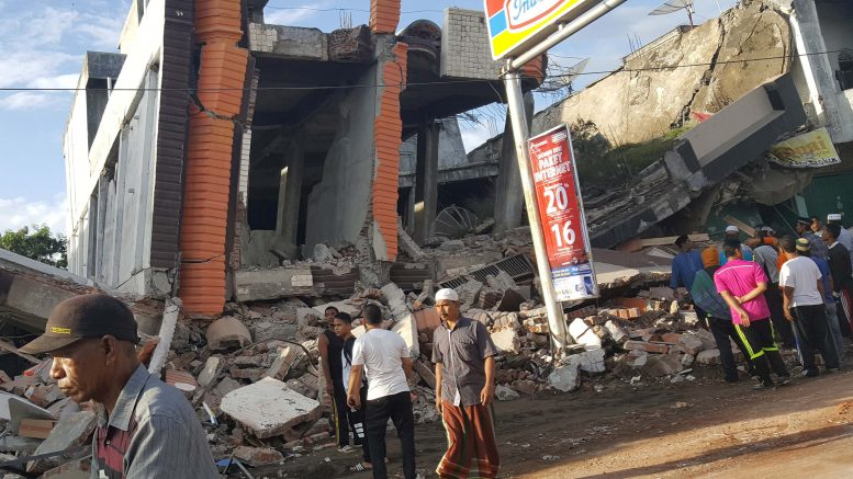 People survey the damage after dozens of buildings collapsed following a 6.4 magnitude earthquake in Ule Glee, Pidie Jaya in the northern province of Aceh, Indonesia