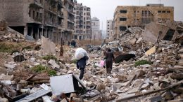 People walk amid the rubble as they carry belongings that they collected from their houses in the government controlled area of Aleppo Security Council