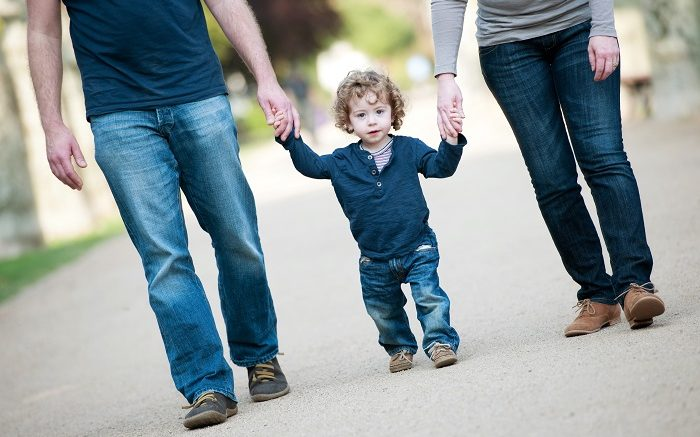Little boy walks with mother and father