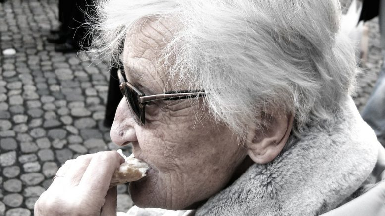Elderly woman eating meal