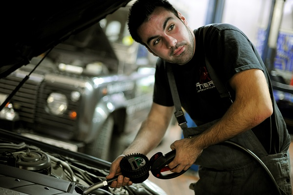 A car mechanic is filling engine oil in a car.