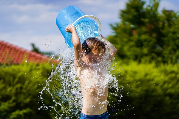 A boy cools down with a bucket of water